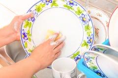 Waschen der Teller im Spülbecken Stockbilder