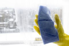 Waschen des Fensters in den gelben Handschuhen, Nahaufnahmehand stockfoto