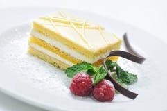 Waschen Sie gelben Kuchen mit Frucht- und Schokoladendekoration auf weißer Platte, Süßspeise, Konditorei, Shop ab Stockfoto