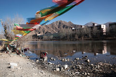 Waschend kleidet außer dem lasa Fluss, unter den Gebetsflaggen Stockfoto