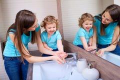 Waschende Babyhände der Mutter lizenzfreie stockfotos
