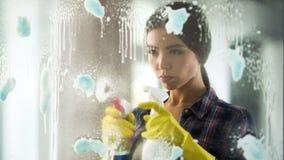 Waschende Fenster Dame und Flecke unter Verwendung der speziellen Substanzen und der Werkzeuge entfernen Lizenzfreies Stockbild