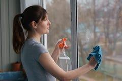 Waschende Fenster der jungen Frau mit einem reinigenden und blauen Lappen Stockbilder