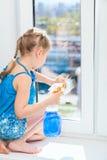 Waschende Fenster mit Lappen und Spray, kleines Mädchen im blauen Kleid Stockfotos