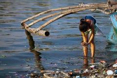 Waschende Hände in beschmutztem philippinischem Fluss Stockbilder
