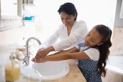 Waschende Hände der Großmutter und der Enkelin stockbild