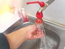 Waschende Hände an der Wanne in der Küche Stockbilder