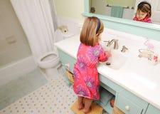 Waschende Hände des jungen Mädchens im Badezimmer stockbilder