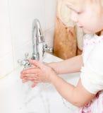 Waschende Hände des kleinen Mädchens Stockfotografie