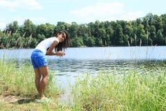 Waschende Hände des Mädchens im See Stockfotos