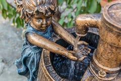 Waschende Hände des Mädchens im Wasserbrunnen Lizenzfreie Stockfotos