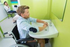 Waschende Hände des Rollstuhlfahrers an der Toilette für Rollstuhlfahrer Lizenzfreie Stockfotografie