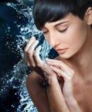 Waschende Hände des schönen weiblichen Modells im Strom des Wassers Stockfoto