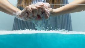Waschende Kleidung der Frau, unter Verwendung der Handpflegeprodukte beim Handeln von Haushaltsaufgaben stock footage