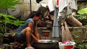 Waschende Kleidung der Hausfrau im unordentlichen Hinterhof stock video