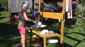 Waschende Kleidung der schönen Dorfbewohnerfrau eigenhändig in der Metallschüssel im Bauernhofyard 4K stock video