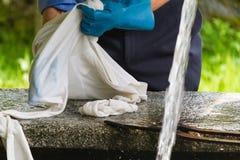 Waschende Kleidung des Mannes der alte Brunnen Stockfoto
