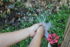 Waschende kleine Hände draußen Stockfotos