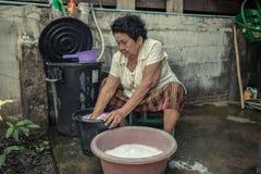 Waschende Stoffe der älteren asiatischen Frau Stockfotos