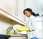 Waschende Teller der jungen Frau Stockbilder