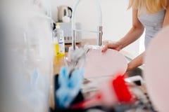 Waschende Teller der jungen Frau in der Wanne stockbilder