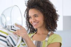 Waschende Teller der schönen jungen Hausfrau mit Schwamm Stockfotografie