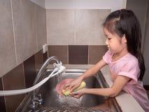 Waschende Teller des entzückenden Kindermädchens in der inländischen Küche lizenzfreies stockbild