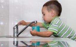 Waschende Teller des kleinen Jungen Stockfotos