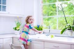 Waschende Teller des kleinen Mädchens Lizenzfreie Stockfotos