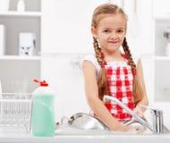 Waschende Teller des kleinen Mädchens in der Küche stockfotografie