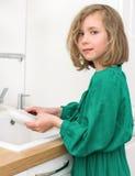 Waschende Teller des kleinen Mädchens Stockbilder