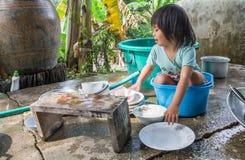 Waschende Teller des Mädchens Stockfoto