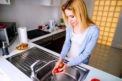 Waschende Tomaten der blonden Frau unter dem Hahn Zubereitung des Frühstücks Lizenzfreie Stockbilder