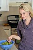 Waschende Trauben der reizvollen jungen blonden Frau in der Küche Stockbild