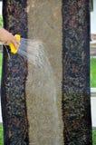 Waschende Wolldecke mit Schlauchsprüher Lizenzfreies Stockfoto
