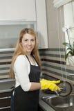 Waschender Teller der jungen Frau in der Küche Stockbilder