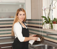 Waschender Teller der jungen Frau in der Küche Lizenzfreies Stockbild
