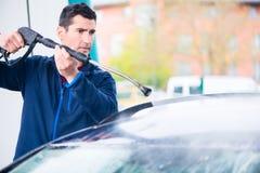 Waschendes Auto der engagierten Arbeitskraft mit Hochdruckschlauch Lizenzfreies Stockfoto