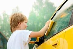 Waschendes Auto des kleinen Jungen. stockfoto
