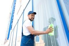 Waschendes Fenster der männlichen Arbeitskraft von der Außenseite Stockfotografie
