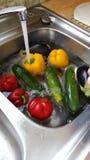 Waschendes Gemüse im Spülbecken Stockbild