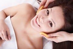 Waschendes Gesicht der Frau durch Schwamm. Stockbilder