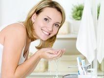 Waschendes Gesicht der Frau mit Wasser Stockbilder