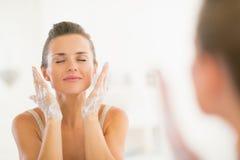 Waschendes Gesicht der jungen Frau im Badezimmer Stockfoto