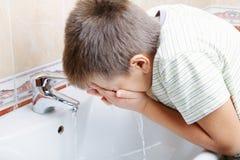 Waschendes Gesicht des Jungen Stockbild