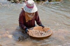 Waschendes Gold der Frau im Fluss Stockbild