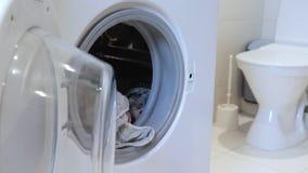 Waschendes Leinen und Kleidung Konzept, Frau setzt schmutzige Kleidung in Waschmaschine ein und schließt sie stock footage