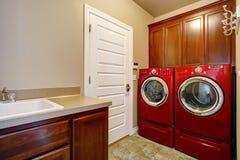 Waschküche mit modernen roten Geräten Stockbilder