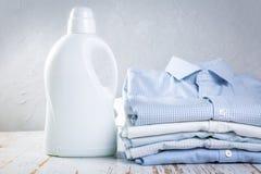 Wasconcept - stapel van gevouwen overhemden met fles wasdetergens royalty-vrije stock afbeelding