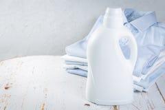 Wasconcept - stapel van gevouwen overhemden met fles wasdetergens royalty-vrije stock afbeeldingen